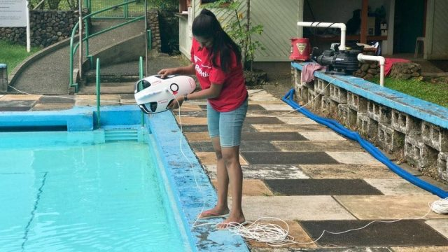 South Pacific Flying Labs' Amrita holding a PowerRay underwater drone.