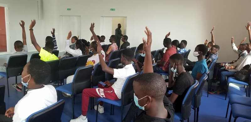 A group of students in a classroom with their hands raised