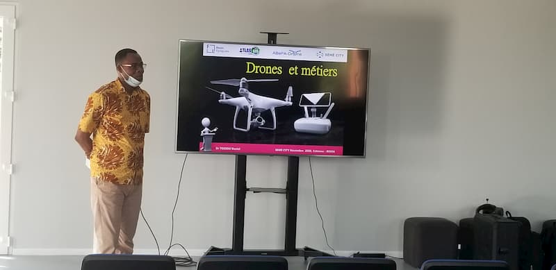 An instructor standing next to a presentation screen with a drone on the presented slide