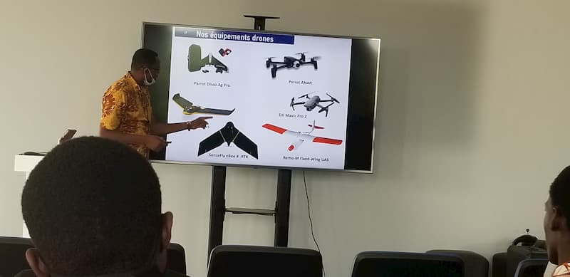 An instructor presenting information about drones from a slide on a screen