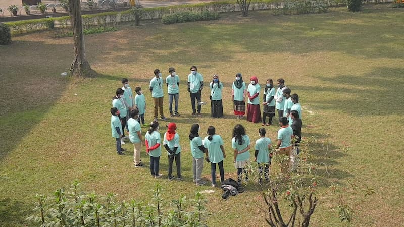 Bangladesh Flying Labs STEM Program: A circle of students watch a drone take flight