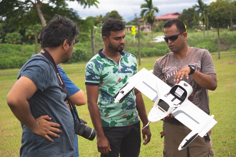 Fiji Flying Labs team reviewing a drone with a group