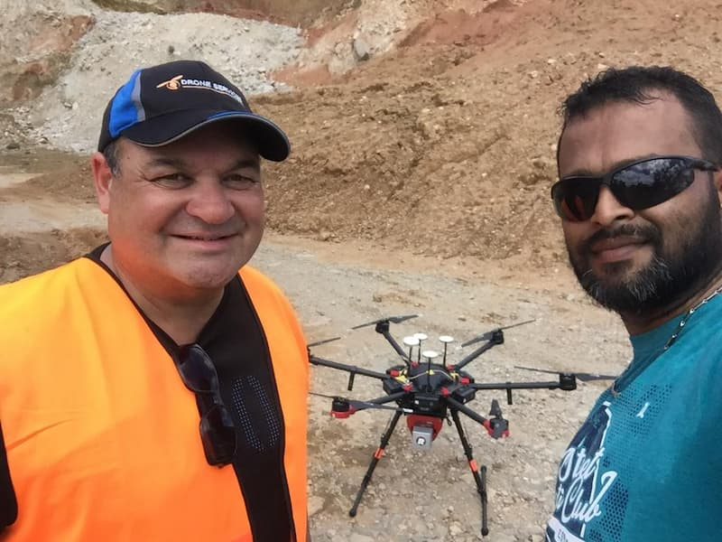 Two Fiji Flying Labs team members posing in front of a landed drone