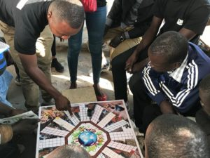 Cameroon Flying Labs - Displaying how to play an environmental game during outreach campaigns